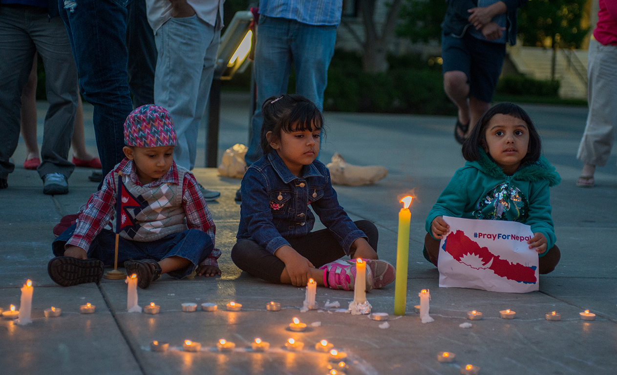 (Left to right) Ryan Pokharey, 3, Aayusha Aryal, 5, and Priyasa Couragain, 4, sit next to the lit candles during the candlelight vigil in Bosco Plaza on April 30, 2015. Many students, faculty, and community members came to remember and honor those affected by the earthquake.